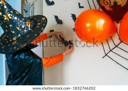 Boy in a black cape and a witch's hat glues a paper bat to the wall. The child decorates the house for Halloween. Royalty-Free Stock Photo #1832766202