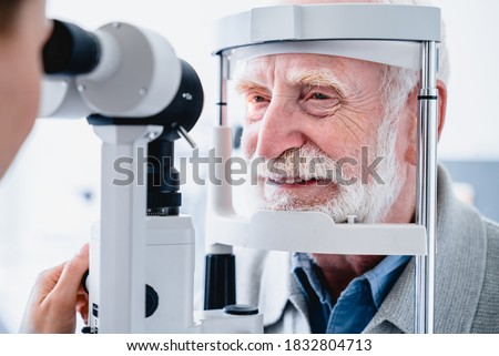 Close up photo of smiling senior male patient during sight examination Royalty-Free Stock Photo #1832804713