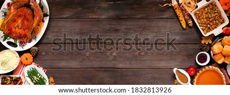 Traditional Thanksgiving turkey dinner. Top view double border on a dark wood banner background with copy space. Turkey, mashed potatoes, dressing, pumpkin pie and sides. Royalty-Free Stock Photo #1832813926