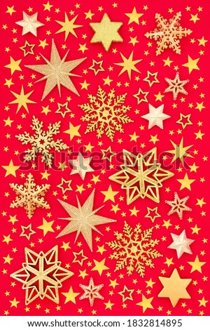 Christmas design of gold stars & snowflakes on red background. Abstract composition for Xmas, New Year & holiday season. Flat lay top view.