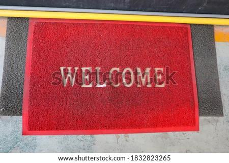 Welcome red mat in front of door, shop. #1832823265