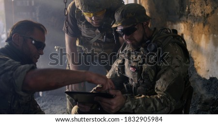Cheerful bearded man in camouflage sharing photos with squad mate while resting inside abandoned building during war