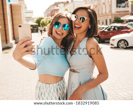 Two young beautiful smiling hipster female in trendy summer clothes.Sexy carefree women posing on the street background in sunglasses. They taking selfie self portrait photos on smartphone at sunset