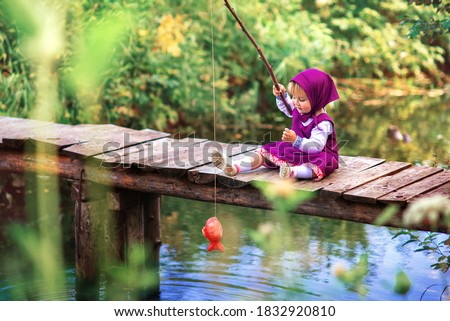 A little girl dressed as Masha from the cartoon Masha and the Bear is fishing on a bridge in the forest. The girl is very similar to Masha and is dressed in a fuchsia-colored sundress and scarf.