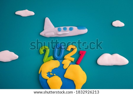 A plane flying over the planet Earth with the year 2021 on it. The scene is made out of polymer clay.