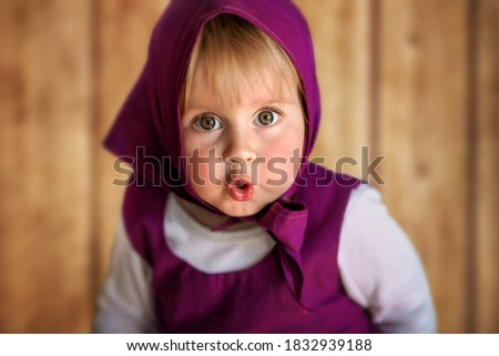 """Horizontal close-up portrait of a little girl with big eyes in Masha's costume from the cartoon """"Masha and the Bear"""". The girl is dressed in a fuchsia sundress and a scarf. Looks into the camera"""
