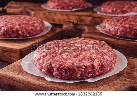 Raw hamburgers on cutting board with wood pile background - Close-up