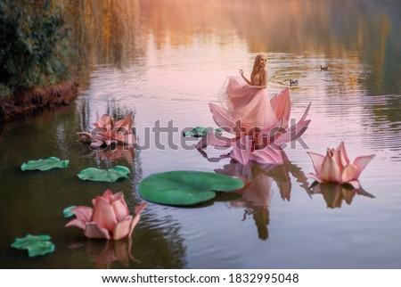 art photo fantasy. Autumn magic miracle. small blonde happy woman princess stands dancing in pink big huge lotus lily flower, on water of river. Short dress. image child of nature. Cartoon character Royalty-Free Stock Photo #1832995048