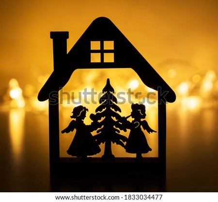 Dark silhouette of Christmas ornament with two cute angel and Christmas tree on a yellow bokeh christmas lights background
