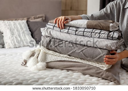 Beautiful woman in winter thick warm robe is sitting and neatly folding bed linens and white bath towels. Organizing and sorting clean laundry. Organic and natural cotton textile. Manufacture. Royalty-Free Stock Photo #1833050710