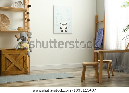 Stylish nursery room interior with picture on wall