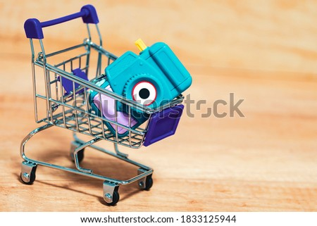 Camera in a basket, cart. The concept of price, purchase of photographic equipment.