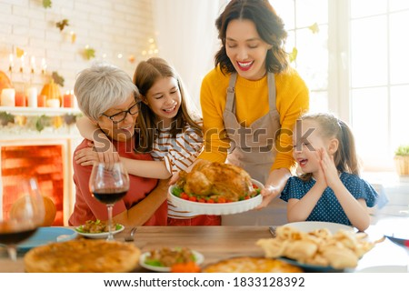 Happy Thanksgiving Day! Autumn feast. Family sitting at the table and celebrating holiday. Traditional dinner. Grandmother, mother and daughters. #1833128392