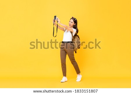 Young pretty Asian tourist girl taking selfie with digital camera in yellow isolated background