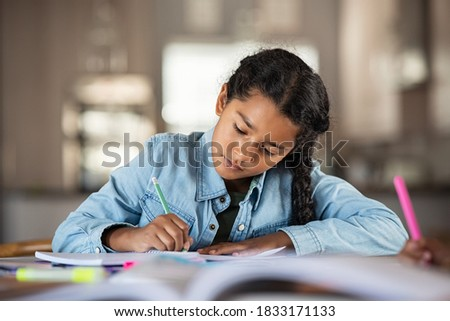 Middle eastern girl doing homework writing and reading at home. Concentrated beautiful indian female child writing in her notebook. Focused latin schoolgirl studying and preparing for exams. Royalty-Free Stock Photo #1833171133