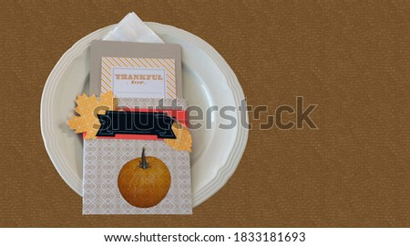 Plate with napkin and greetings card for thanksgiving dinner celebration. Copyspace