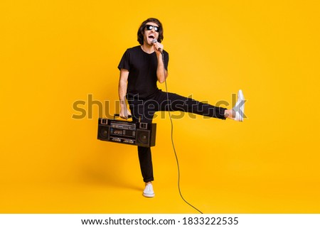 Full length photo of young man hold vintage radio mic open mouth raise leg wear black t-shirt pants white sneakers glasses isolated yellow color background Royalty-Free Stock Photo #1833222535