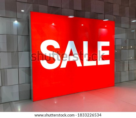 Red banner in the showcase with inscription SALE. Glass showcase. Shopping center. Black Friday