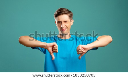 Blaming male portrait. Dislike gesture. Loser failure. Condemnation shame. Bad job. Disappointed man showing thumb down looking at camera isolated on blue. Royalty-Free Stock Photo #1833250705