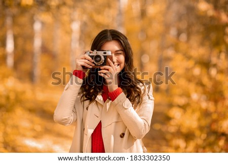 Portrait of happy female photographer with retro camera taking pictures of beautiful autumn at park. Lovely millennial lady photographing nature during her walk outside on sunny day