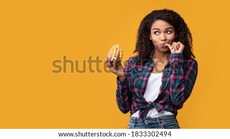 Cheat Meal. Portrait Of Happy African American Casual Woman Eating Tasty Burger, Licking Finger, Looking Away At Copy Space. Satisfied Woman Holding Fastfood, Isolated Over Orange Background, Banner Royalty-Free Stock Photo #1833302494