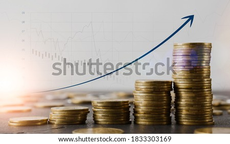 Financial growth concept. Stacks of gold coins on table and raising arrow over economic charts and diagrams on background, creative collage for business success or profit achievement, copy space Royalty-Free Stock Photo #1833303169
