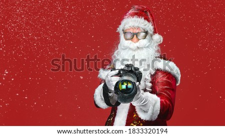 cool Santa Claus taking holiday pictures - isolated on the red b