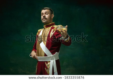 Cocktail drinking. Young man in suit as Nicholas II isolated on dark green background. Retro style, comparison of eras concept. Beautiful male model like historical character, monarch, old-fashioned. Royalty-Free Stock Photo #1833355876
