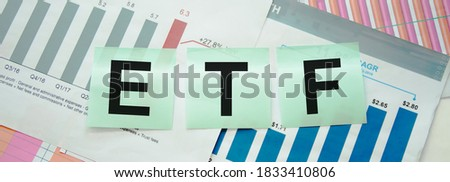ETF, exchange-traded fund an investment fund traded on stock exchanges concept, multi color arrows pointing to the word ETF at the center of black cement chalkboard wall. High quality photo