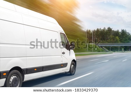 White modern delivery small shipment cargo courier van moving fast on motorway road to city urban suburb. Busines distribution and logistics express service. Mini bus driving on highway on sunny day #1833429370