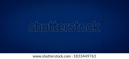 Beautiful Abstract Grunge Decorative Navy Blue Dark Stucco Wall Background. Image of the dark colored concrete wall has light from the center of the picture. There is space for designing and text.