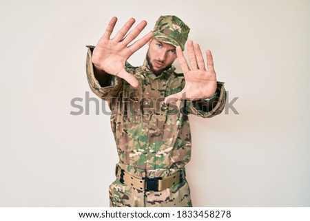 Young caucasian man wearing camouflage army uniform doing frame using hands palms and fingers, camera perspective