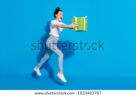 Full length profile side photo crazy girl jump hold green gift box run want give dream package friend 14-ferbuary 8-march holiday wear white t-shirt isolated bright shine color background Royalty-Free Stock Photo #1833483787