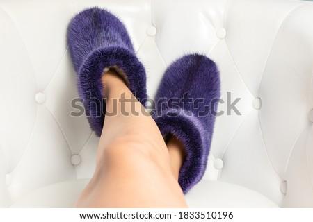 Beautiful fluffy fur footwear on women legs. Royalty-Free Stock Photo #1833510196