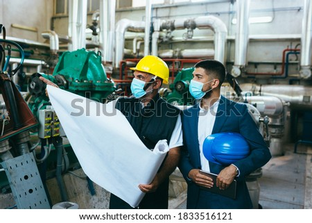 industrial workers looking at the blueprints, covid protected, wearing face mask Royalty-Free Stock Photo #1833516121