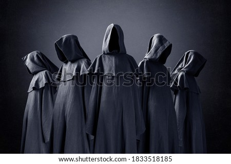 Group of five scary figures in hooded cloaks in the dark Royalty-Free Stock Photo #1833518185