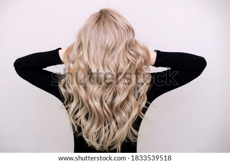 Female back with long, curly, natural blonde hair, in black dress, on grey background