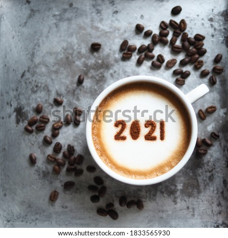 White cup with coffee and number 2021 over frothy surface serving in rustic aluminum tray with coffee beans and space for text. New year new you, Holidays food art theme Happy New Year 2021. (square) #1833565930