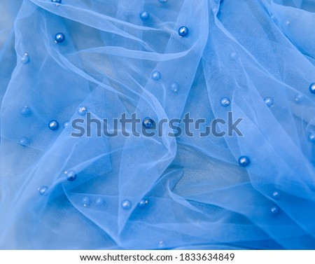 Close up picture of blue tulle fabric with pearls. Background from sky blue crumpled tulle with small beads. Abstract wallpaper for fashion industry. Beautiful transparent blue shade of tulle.