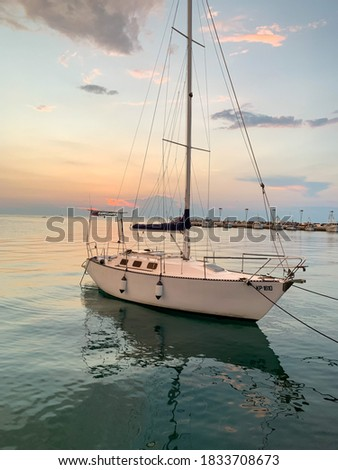Picture of a white sailing boat with a beautiful sunset in the background