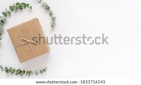 Soft pastel craft paper gift box with eucalyptus branches on white background