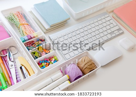 Stylish colored stationery in pastel colors. Female workplace. Organization of a drawer at the workplace. Storage and order of office supplies. Concept back to school. Royalty-Free Stock Photo #1833723193