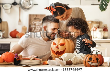 Cheerful multi ethnic family parents with son smiling  while creating jack o lantern from pumpkin during Halloween celebration in kitchen at home Royalty-Free Stock Photo #1833746497