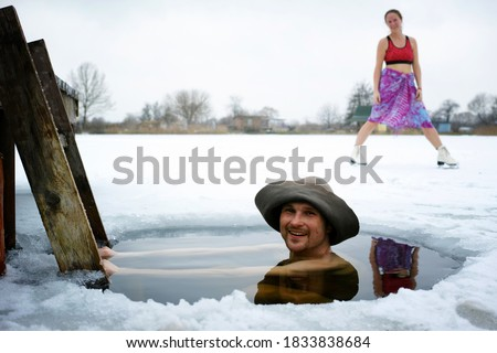 Young couple enjoying winter holidays and tempered in cold water and snow after a Russian bath                      #1833838684
