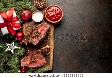 Christmas Dinner for Two. Baked Beef on the Bone with Spices on a Stone Table with a Christmas Tree and New Year's Toys with copy space for your text #1833838723