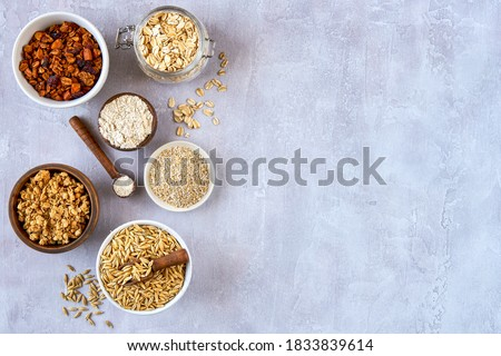 Oat products assortment in bowls. Granola, rolled oats, bran , flour and raw oat seeds . Top view #1833839614