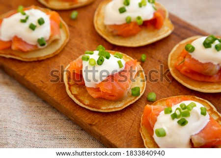 Homemade Blini with Smoked Salmon, Creme and Chives on a rustic wooden board, low angle view. Close-up. Royalty-Free Stock Photo #1833840940