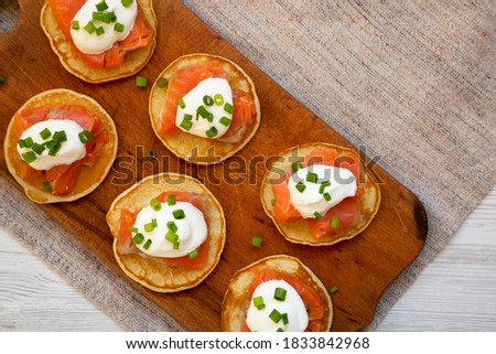Homemade Blini with Smoked Salmon, Creme and Chives on a rustic wooden board, view from above. Copy space. Royalty-Free Stock Photo #1833842968