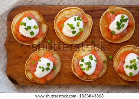 Homemade Blini with Smoked Salmon, Creme and Chives on a rustic wooden board, top view. Flat lay, overhead, from above. Royalty-Free Stock Photo #1833843868