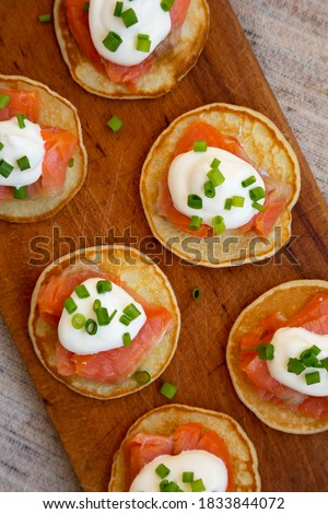 Homemade Blini with Smoked Salmon, Creme and Chives on a rustic wooden board, overhead view. Flat lay, top view, from above. Royalty-Free Stock Photo #1833844072